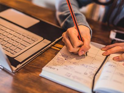 photo d'un ordinateur portable ouvert et main d'une personne écrivant dans un agenda