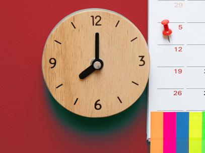 photo d'une horloge sur fond rouge à côté un calandrer indiquant une date importante
