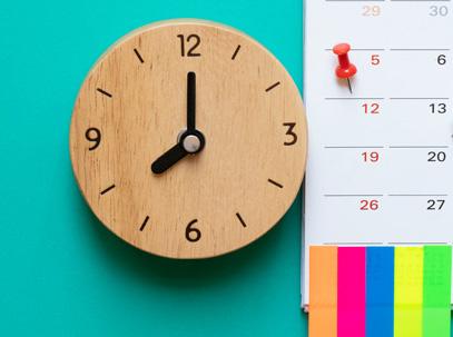 photo d'une horloge sur fond vert à côté un calandrer indiquant une date importante
